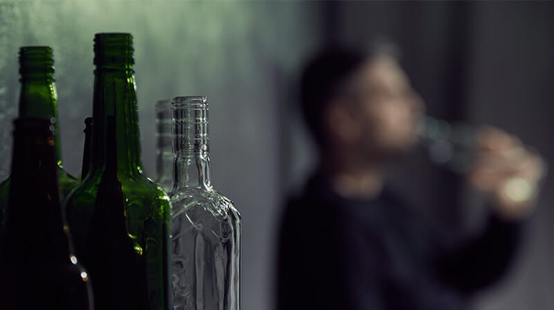 man near alcohol bottles struggling with an alcohol addiction