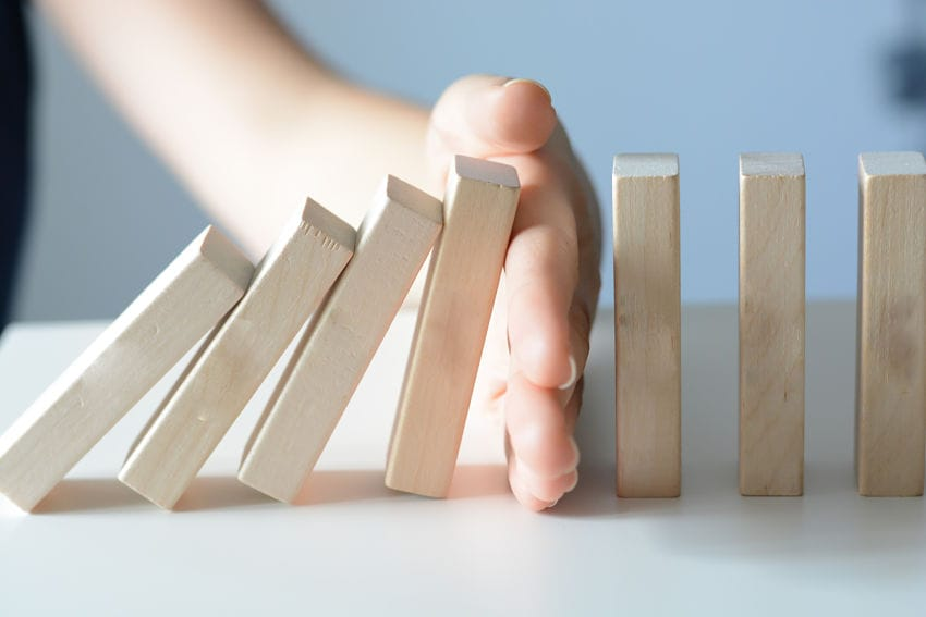 hand stopping the domino effect of addiction and intervention