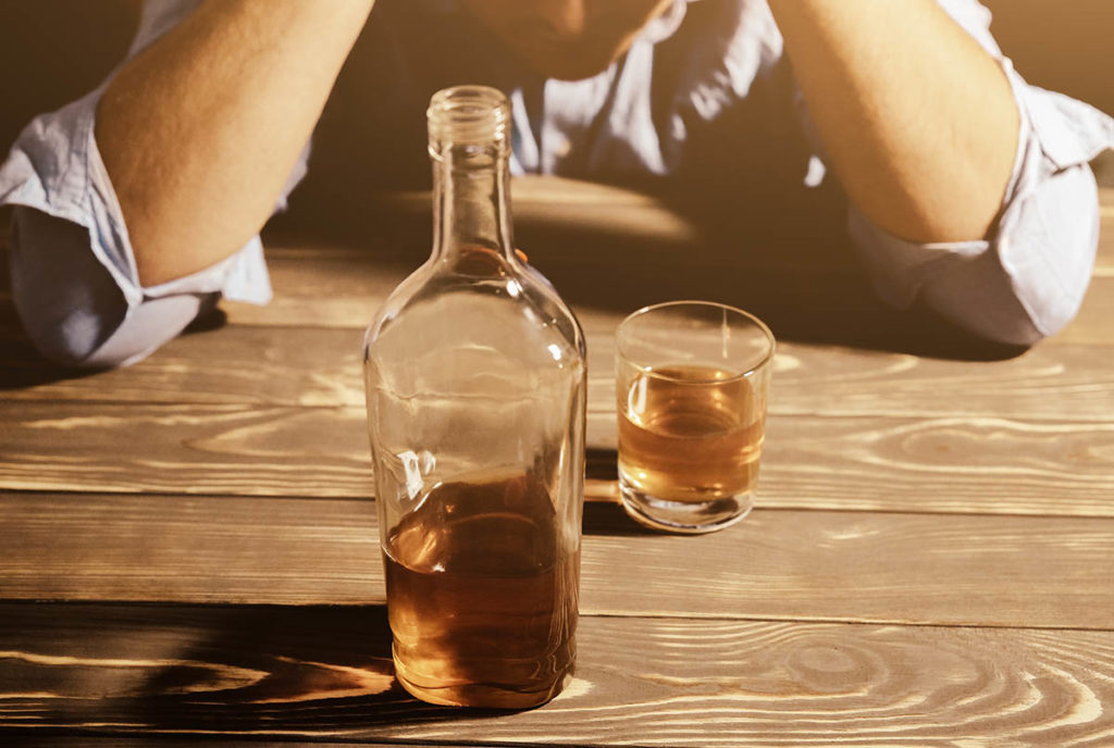 a person drinking a bottle of whiskey by themselves showing signs of alcoholism