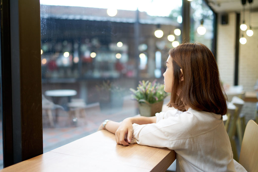 young woman staring out cafe window curious about different types of addiction